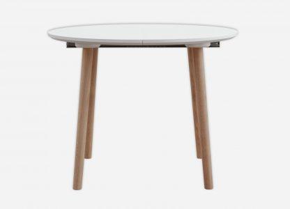 Rundt spisebord med udtræk med hvid laminat og bordben i egetræ