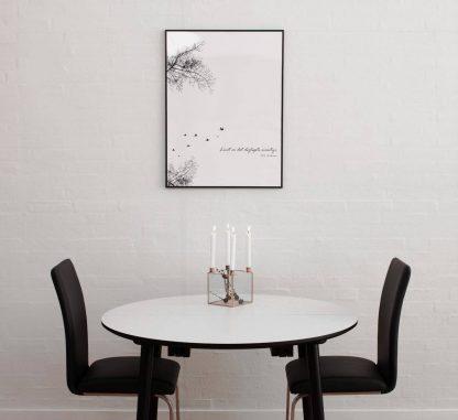 Rundt spisebord med udtræk med hvid bordplade og sorte bordben