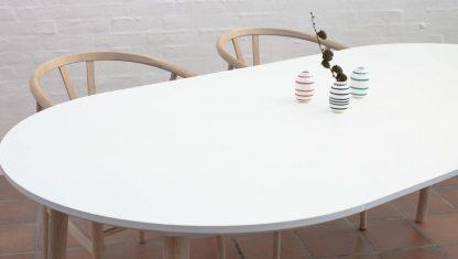 Rundt spisebord med udtræk med hvid bordplade og egetræsben