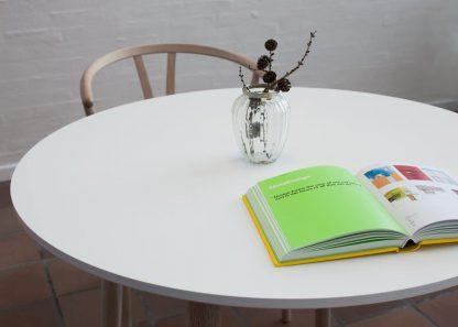 Rund spisebord med hvid bordplade og egetræsben