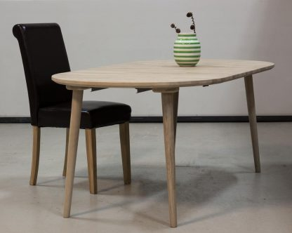 Rundt egetræsbord med udtræk her vist med isat tillægsplader