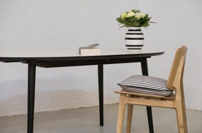 Ellipse spisebord med udtræk her vist med hvid laminat og sorte ben